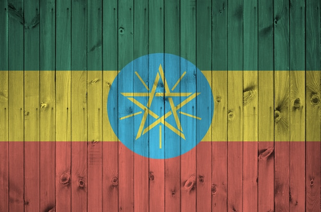 Flaga etiopii przedstawiona w jasnych kolorach farby na starej drewnianej ścianie. teksturowane transparent na szorstkim tle