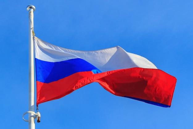 Flaga federacji rosyjskiej na tle błękitnego nieba. macha flagą rosji