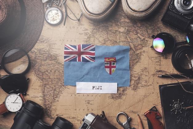 Flaga fidżi między akcesoriami podróżnika na starej mapie vintage. strzał z góry