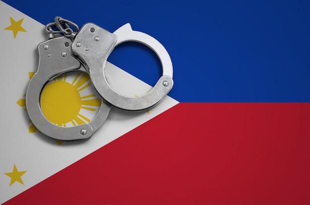 Flaga filipin i kajdanki policyjne. pojęcie przestępczości i przestępstw w kraju