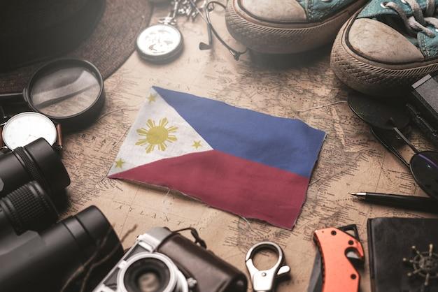 Flaga filipin między akcesoriami podróżnika na starej mapie vintage. koncepcja miejsca turystycznego.