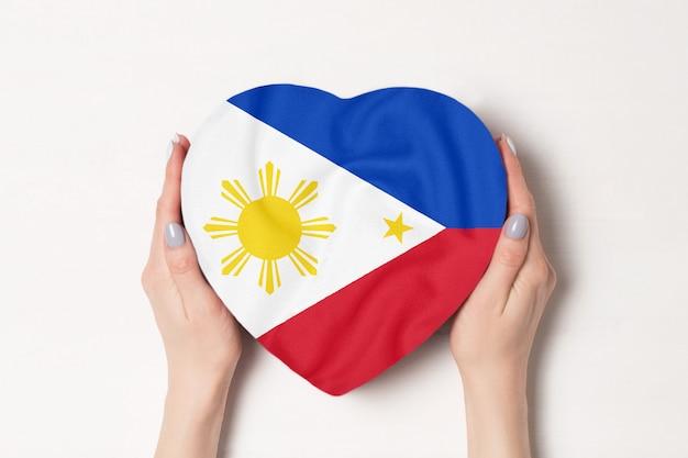 Flaga filipin na pudełku w kształcie serca w rękach kobiet.