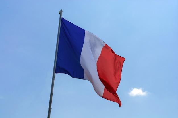 Flaga francja przeciw niebieskiemu niebu z chmurami