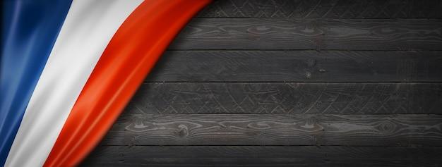 Flaga francji na czarnej ścianie z drewna. poziomy baner panoramiczny.