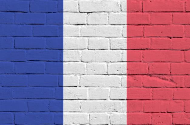 Flaga francji przedstawiona w kolorach farb na starym murem. textured sztandar na dużym ściana z cegieł kamieniarstwa tle
