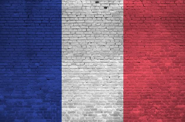 Flaga francji przedstawiona w kolorach farb na starym murem.