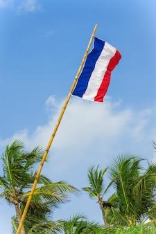 Flaga francji wiejący wiatr na tle błękitnego nieba ekstremalne zbliżenie.