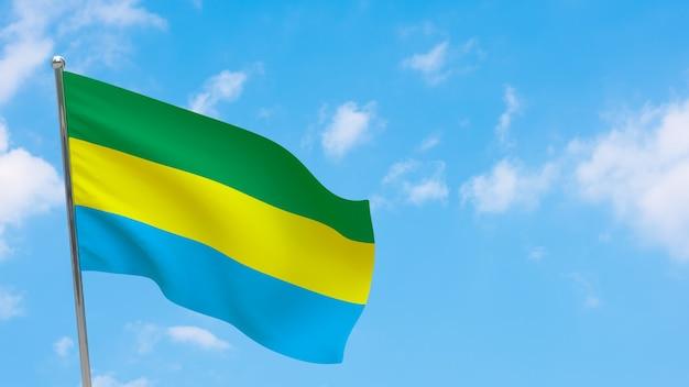 Flaga gabonu na słupie. niebieskie niebo. flaga narodowa gabonu