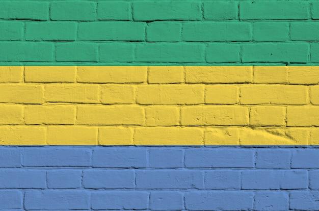 Flaga gabonu przedstawiona w kolorach farb na starym murem.