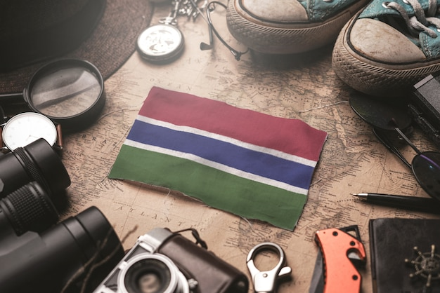 Flaga gambii między akcesoriami podróżnika na starej mapie vintage. koncepcja miejsca turystycznego.