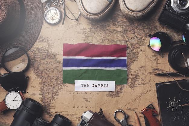 Flaga gambii między akcesoriami podróżnika na starej mapie vintage. strzał z góry