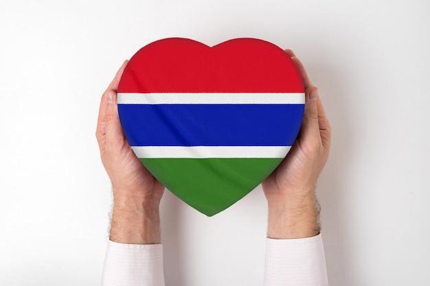 Flaga gambii na pudełku w kształcie serca w męskich rękach.