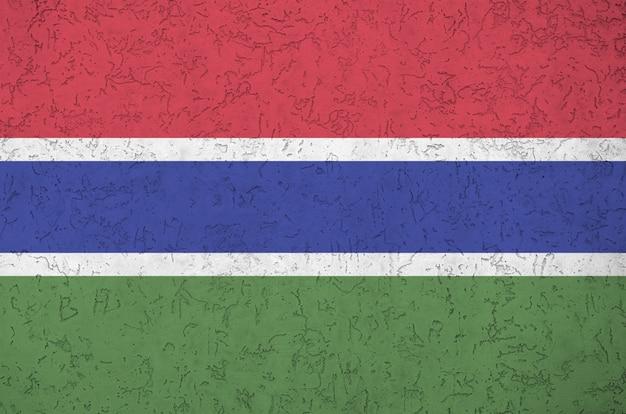 Flaga gambii przedstawiona w jasnych kolorach farby na starej reliefowej ścianie tynkowej. teksturowane transparent na szorstkim tle