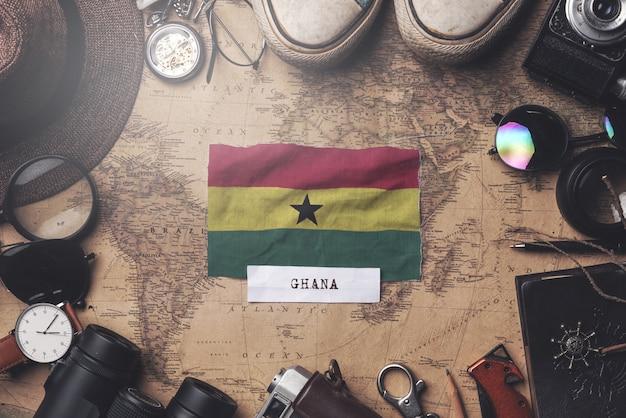 Flaga ghany między akcesoriami podróżnika na starej mapie vintage. strzał z góry