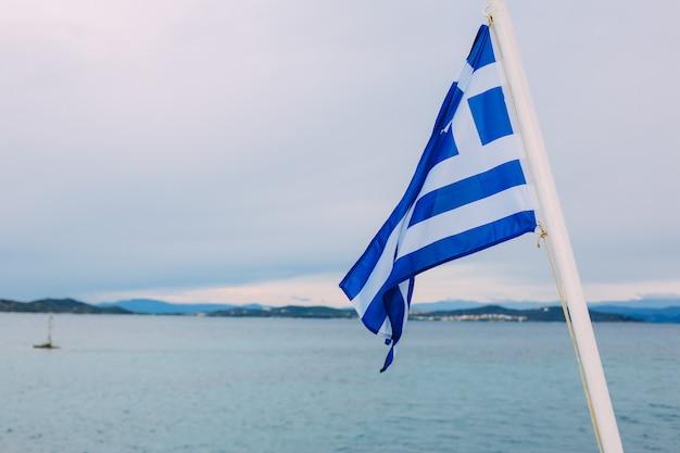 Flaga grecji na statku przed zachmurzonym niebie