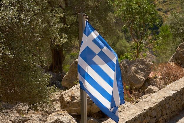 Flaga grecji w górach w pobliżu kamiennego muru.