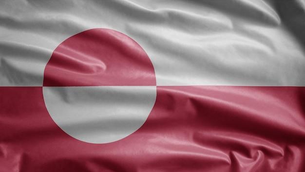 Flaga grenlandii powiewa na wietrze. zbliżenie na baner grenlandii dmuchanie, miękki i gładki jedwab. tkanina tkanina tekstura tło chorąży. użyj go do koncepcji świąt narodowych i okazji krajowych.