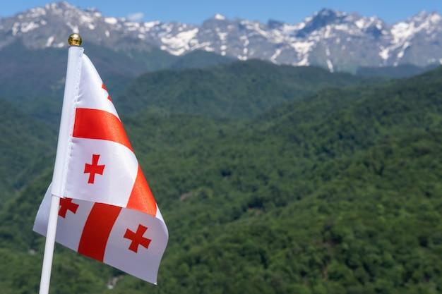 Flaga gruzji macha na tle gór i błękitnego nieba