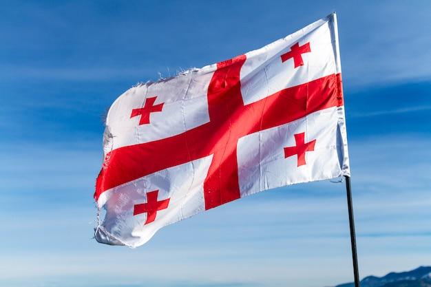 Flaga gruzji macha na wietrze na powierzchni błękitne, czyste niebo