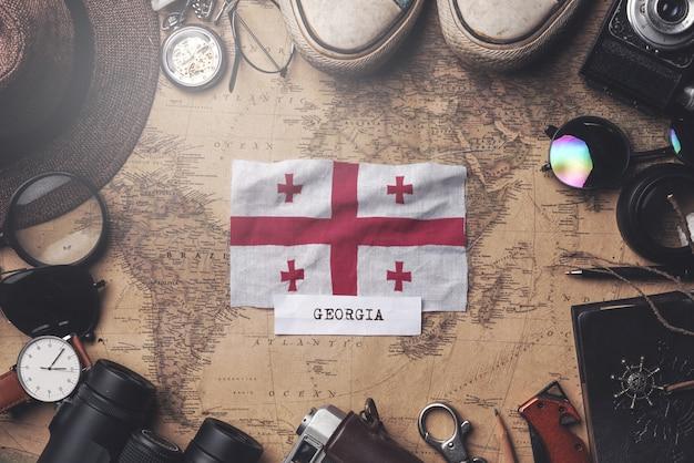 Flaga gruzji między akcesoriami podróżnika na starej mapie vintage. strzał z góry