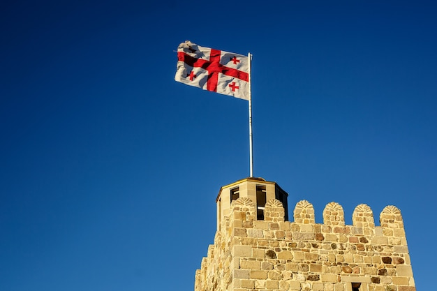 Flaga gruzji na dachu starożytnej wieży na tle błękitnego nieba