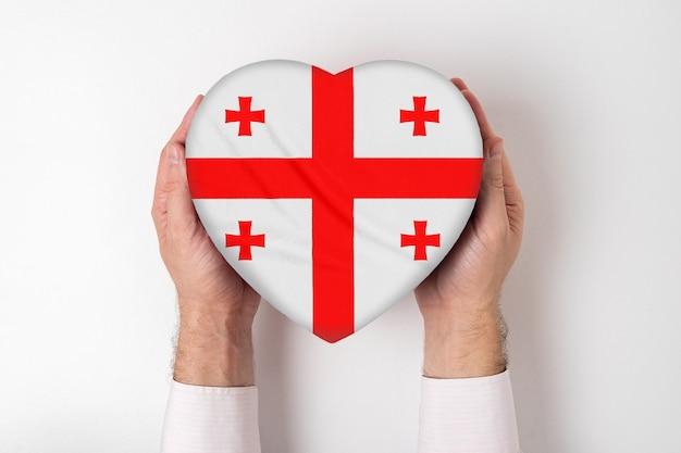 Flaga gruzji na pudełku w kształcie serca w męskich rękach
