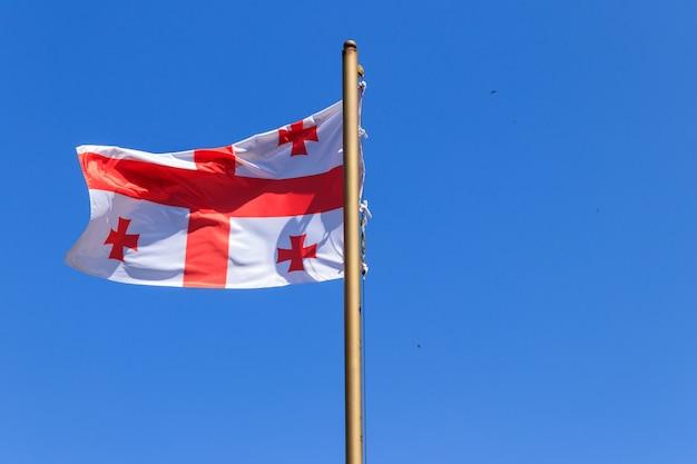 Flaga gruzji na tle błękitnego nieba