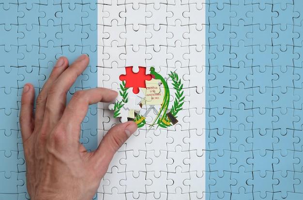 Flaga gwatemali jest przedstawiona na układance, którą ręka mężczyzny kończy, aby ją spasować