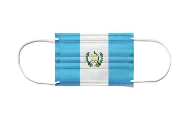 Flaga gwatemali na jednorazowej masce chirurgicznej. biała powierzchnia na białym tle