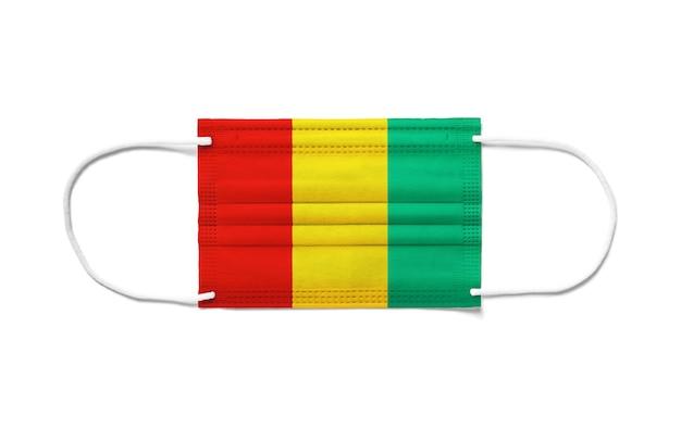 Flaga gwinei na jednorazowej masce chirurgicznej. biała powierzchnia na białym tle