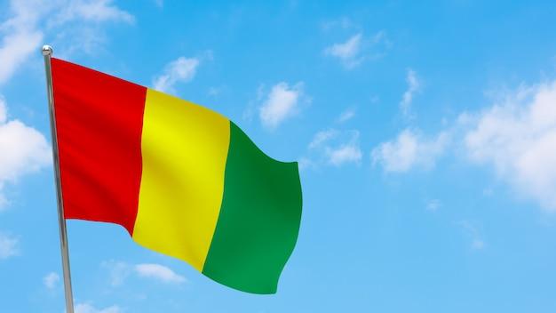 Flaga gwinei na słupie. niebieskie niebo. flaga narodowa gwinei