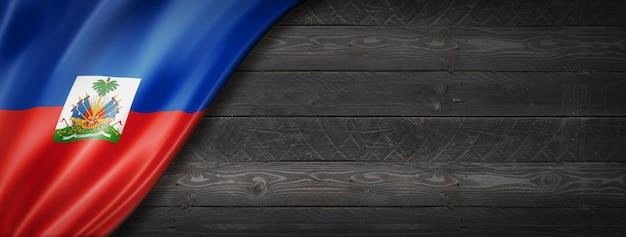 Flaga haiti na czarnej ścianie z drewna. poziomy baner panoramiczny.