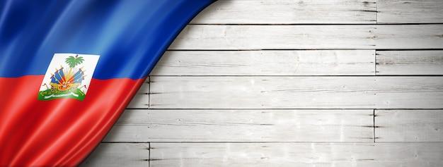 Flaga haiti na starej białej ścianie. poziomy baner panoramiczny.