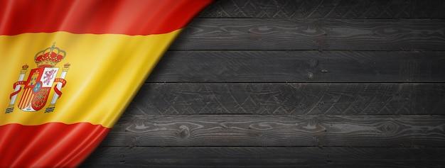 Flaga hiszpanii na czarnej ścianie z drewna. poziomy baner panoramiczny.