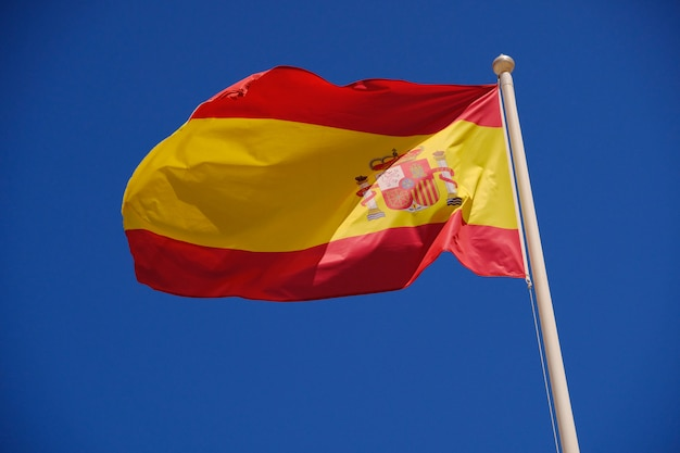 Flaga hiszpanii na tle błękitnego nieba