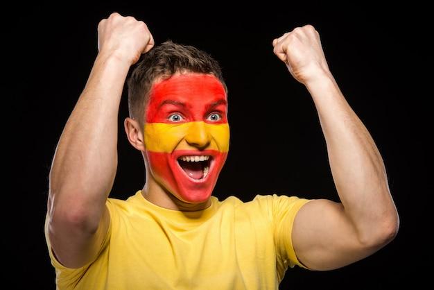 Flaga hiszpanii namalowana na twarzy mężczyzny.