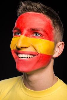 Flaga hiszpanii namalowana na twarzy młodego uśmiechniętego mężczyzny.