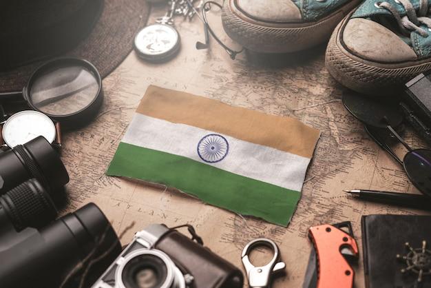 Flaga indii między akcesoriami podróżnika na starej mapie vintage. koncepcja miejsca turystycznego.