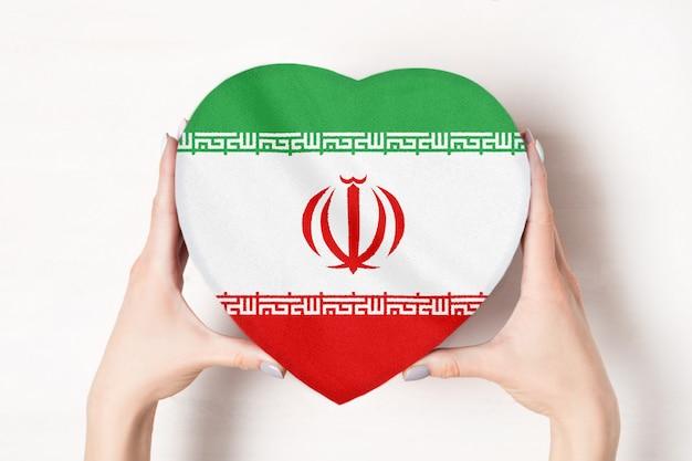 Flaga iranu na pudełku w kształcie serca w rękach kobiet