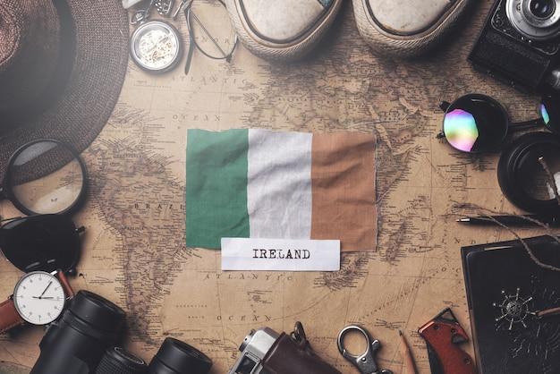 Flaga irlandii między akcesoriami podróżnika na starej mapie vintage. strzał z góry