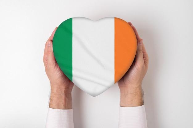 Flaga irlandii na pudełku w kształcie serca w męskich rękach. białe tło