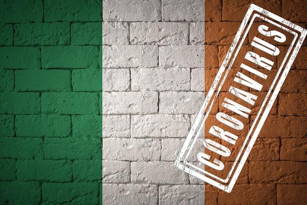 Flaga irlandii o oryginalnych proporcjach. opieczętowane koronawirusem. cegła ściana tekstur. koncepcja wirusa koronowego. na skraju pandemii covid-19 lub 2019-ncov.