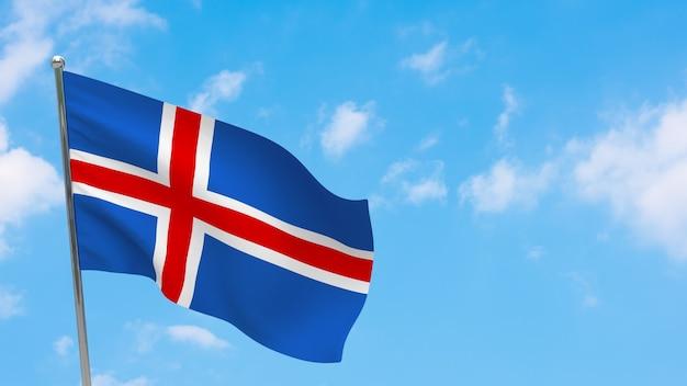 Flaga islandii na słupie. niebieskie niebo. flaga narodowa islandii