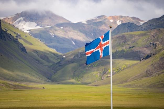 Flaga islandii na tle zielonych gór i błękitnego nieba.
