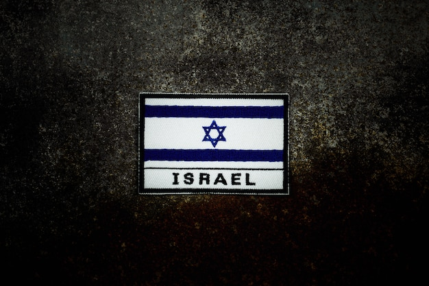 Flaga izraela na zardzewiałej opuszczonej podłodze metalowej w ciemności.