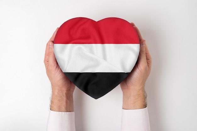 Flaga jemenu na pudełku w kształcie serca w męskich rękach.