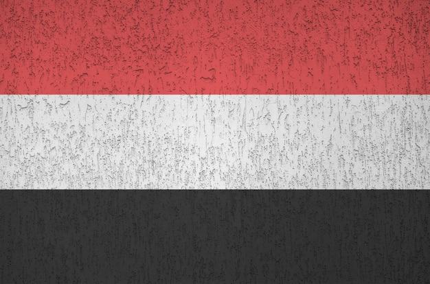 Flaga jemenu przedstawiona w jasnych kolorach farby na starej reliefowej ścianie tynkarskiej. teksturowane transparent na szorstkim tle