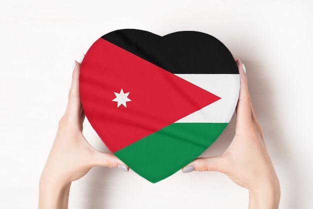 Flaga jordanii na pudełku w kształcie serca w rękach kobiet