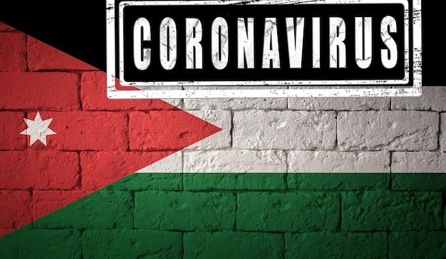 Flaga jordanu o oryginalnych proporcjach. opieczętowane koronawirusem. cegła ściana tekstur. koncepcja wirusa koronowego. na skraju pandemii covid-19 lub 2019-ncov.