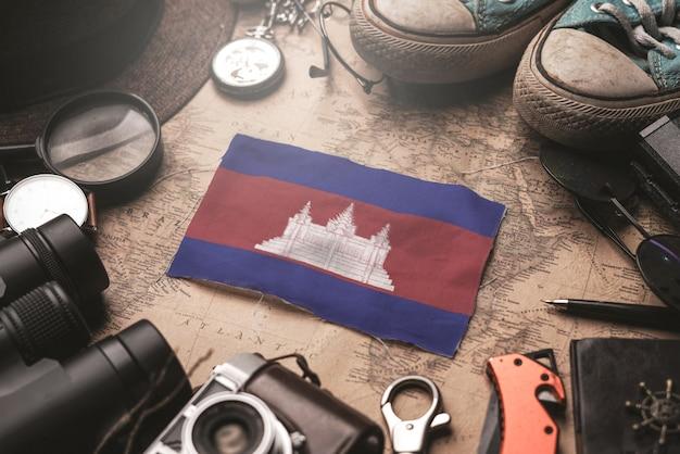 Flaga kambodży między akcesoriami podróżnika na starej mapie vintage. koncepcja miejsca turystycznego.